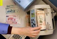 Кассир пересчитывает белорусские рубли в банке в Минске 29 января 2010 года. Белоруссия отпускает национальную валюту в свободное плавание с середины сентября, объявил президент переживающей финансовый кризис страны на совещании с правительством и Нацбанком.   REUTERS/Vasily Fedosenko