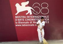 """Funcionária limpa cartaz do Festival de Cinema de Veneza. O tapete vermelho está estendido e os trabalhadores estão dando os últimos toques na sede do evento para a fulgurante abertura na quarta-feira, quando o drama """"The Ides of March"""", com George Clooney, terá sua première. 30/08/2011  REUTERS/Alessandro Bianchi"""