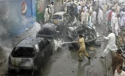 Firefighters spray water on damaged vehicles at the site of a car bomb blast in Quetta August 31, 2011.  REUTERS/Naseer Ahmed