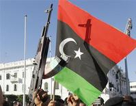 <p>A Kingdom of Libya flag is raised as Libyan Muslims react during Eid prayers at Green Square in Tripoli August 31, 2011. REUTERS/Louafi Larbi</p>