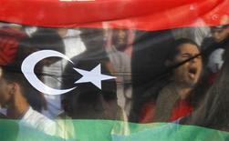 Ливийцы держат флаг королевства Ливия во время молитв по случаю Ид аль-Фитра на Зеленой площади в Триполи, 31 августа 2011 года. Россия признала Национальный переходный совет законной властью Ливии накануне международной конференции, на которой будет обсуждаться становление нового ливийского государства. REUTERS/Louafi Larbi