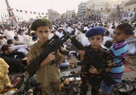Libyan boys pose with toy guns as they gather during the first day of Eid al-Fitr near the courthouse in Benghazi August 31, 2011. REUTERS/Esam Al-Fetori