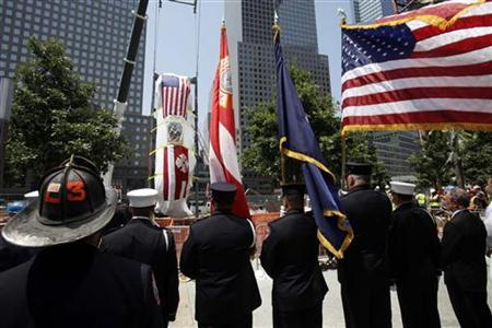Firefighters and other dignitaries, including Fire Commissioner Salvatore Cassano (4th L), 9/11 Memorial President Joe Daniels (5th L) and Mayor Michael Bloomberg (6th L), watch as the Fire Department of New York (FDNY) Ladder Company 3 fire truck, which was partially destroyed in the September 11, 2001 attacks on the World Trade Center, is lowered into an opening in the World Trade Center site below ground level, where it will become part of the permanent installation exhibit in the 9/11 Memorial and Museum in New York July 20, 2011. REUTERS/Seth Wenig/Pool