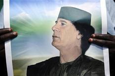 Женщина держит портрет Муаммара Каддафи перед посольством Венгрии в Триполи, 11 августа 2011 года. Муаммар Каддафи призвал своих сторонников бороться до конца, в то время как мировые лидеры выделили несколько миллиардов долларов в помощь новой ливийской власти. REUTERS/Paul Hackett