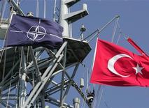 Флаги Турции (справа) и НАТО на военном корабле в Стамбуле, 26 июня 2004 года. Турция разместит на своей территории радар системы раннего предупреждения НАТО об опасности ракетного нападения с целью повышения безопасности стран альянса, сообщил турецкий МИД. REUTERS/Fatih Saribas