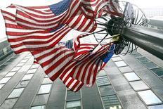 """Американские флаги около офисного здания в Нью-Йорке, 12 марта 2008 года. Агентство, контролирующее ипотечные рынки США, готовится подать иски против более десятка крупных банков, обвиняя их в том, что они давали ложную информацию о качестве закладных, которые оформляли и продавали во время формирования """"пузыря"""" на жилищном рынке, сообщила газета New York Times. REUTERS/Mike Segar"""