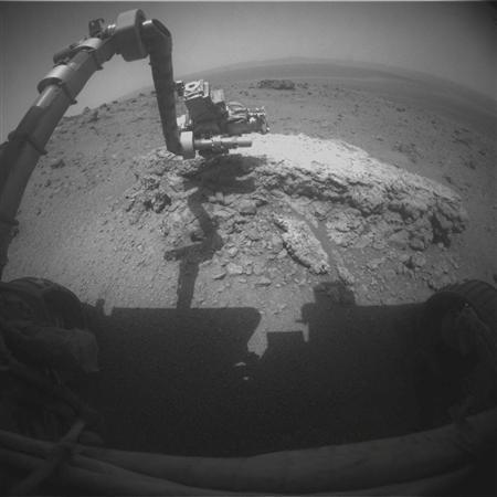 The arm of NASA's Mars Exploration Rover Opportunity is seen extended toward a light-toned rock, ''Tisdale 2'', during the 2,695th Martian day, or ''sol'', of the rover's work on Mars, in this picture taken by the rover's front hazard-avoidance camera on August 23, 2011. The rock, ''Tisdale 2'', is about 12 inches (30 cm) tall. The rover used two instruments on the robotic arm, the microscopic imager and the alpha particle X-ray spectrometer, to examine Tisdale 2. In this image, the turret at the end of the arm is positioned so that the microscopic imager is facing the rock. REUTERS/NASA/JPL-Caltech/Handout
