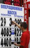 Сотрудник операционной кассы меняет цифры на табло в Москве, 9 августа 2011 года. Рубль торгуется в узких диапазонах с убытком к валютной корзине и её компонентам на фоне глобального отторжения риска перед важной публикацией американской трудовой статистики. REUTERS/Sergei Karpukhin