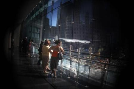 A woman looks through a viewing window of the World Trade Center site in New York, August 11, 2011. This image was taken with a Holga lens mounted on a DSLR camera. REUTERS/Shannon Stapleton