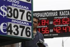 Мужчина меняет вывеску пункта обмена валюты в Москве 10 августа 2011 года. Рубль дешевеет в начале торгов вторника, копируя динамику валют товарной группы, снижающихся на фоне бегства от риска и падения цен на сырье из-за опасений замедления роста глобальной экономики. REUTERS/Sergei Karpukhin