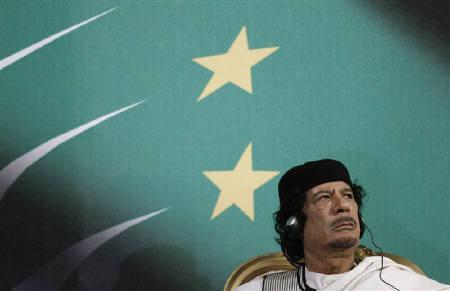 Ousted Libyan leader Muammar Gaddafi looks on as Italy's Prime Minister Silvio Berlusconi gives a speech in Rome August 30, 2010. REUTERS/Max Rossi/Files