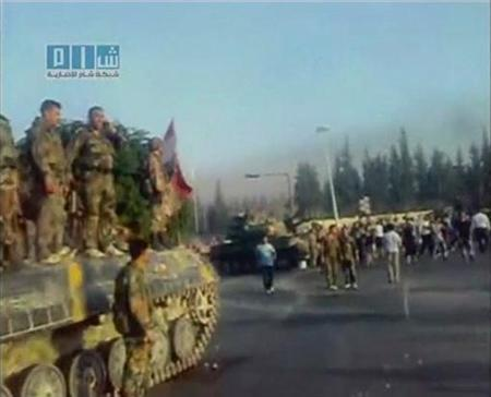 EDITOR'S NOTE: REUTERS CANNOT INDEPENDENTLY VERIFY CONTENT OF THE VIDEO FROM WHICH THIS STILL IMAGE WAS TAKEN. Army defectors stand atop a tank as residents gather in Hama in this still image taken from video July 31, 2011. REUTERS/YouTube via Reuters TV