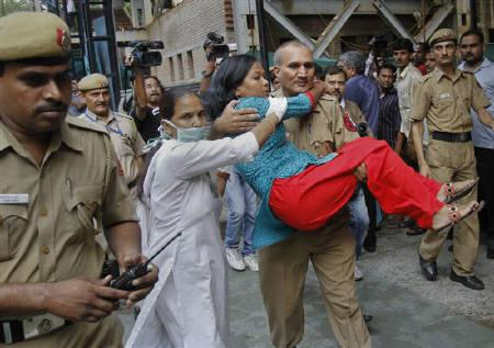 A nurse tries to assist as a policeman carries a woman, who was injured by a blast outside the High Court, towards a hospital for treatment in New Delhi September 7, 2011. REUTERS/Vijay Mathur