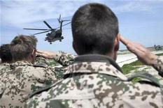 Немецкие солдаты отдают честь на фоне улетающего с телами их товарищей вертолета в Афганистане 4 апреля 2010 года. Проблемы, с которыми столкнутся Центральная Азия и Россия с уходом США из Афганистана, идентичны тем, что оставил после себя СССР, сказал в среду генсек ОДКБ, посоветовав Западу вооружиться советским опытом. REUTERS/Bundesregierung/Steffen Kugler/Handout