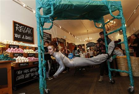 British performance artist Alice Newstead suspends from shark hooks pierced through her back at a cosmetic shop in San Francisco, California August 24, 2011. REUTERS/Robert Galbraith