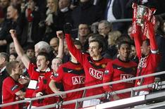 Manchester United's Patrice Evra (R) celebrates with teammates as he lifts the trophy after defeating Aston Villa during the English League Cup final soccer match at Wembley Stadium in London, February 28, 2010.   REUTERS/Darren Staples