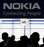 Посетители выставки CommunicAsia возле стенда Nokia, Сингапур, 21 июня 2011 года. Растущий спрос на устройства iPhone компании Apple и телефоны на базе ОС Android Google привел к росту продаж смартфонов в Западной Европе на 48 процентов во втором квартале по сравнению с предыдущим годом, оставив позади экс-лидера рынка Nokia. REUTERS/Tim Chong