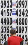 Работник обменного пункта в Москве меняет курсы валют, 9 августа 2011 года. Рубль оставался в минусе к бивалютной корзине вечером в четверг, сменив знаки в кросс-курсах с евро и долларом после заседания ЕЦБ и отразив динамику главной валютной пары. REUTERS/Sergei Karpukhin
