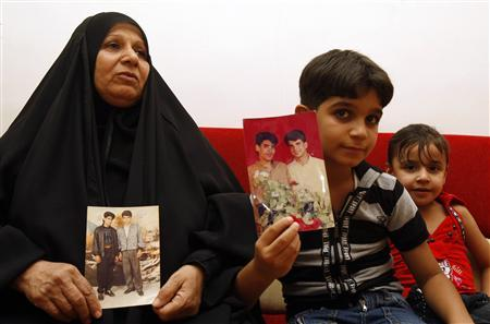 The mother and son of Baha Mousa (R in the picture), an Iraqi hotel receptionist who was kicked and beaten to death whilst in British Army custody, hold pictures of him at their house in Basra, 420 km (260 miles) southeast of Baghdad September 7, 2011. REUTERS/Atef Hassan
