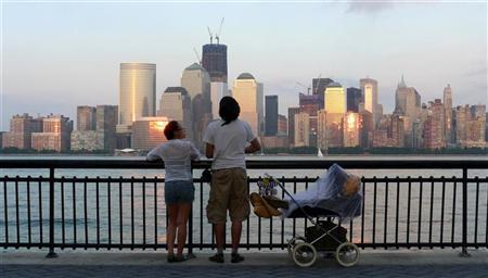 A couple look out at the skyline of New York's Lower Manhattan from a promenade in Jersey City, New Jersey, August 20, 2011. REUTERS/Gary Hershorn