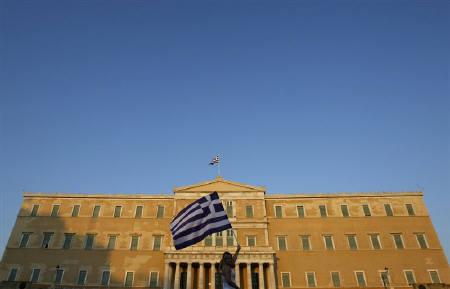 A woman raises a Greek flag in front of the parliament at Constitution square in Athens June 30, 2011. A debt swap meant to help Greece avoid default hung in the balance on Friday with expectations of take-up by private creditors slipping amid fierce European pressure on Athens. REUTERS/John Kolesidis/Files