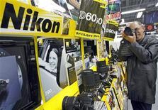 Посетитель магазина в Токио рассамтривает фотоаппараты Nikon, 5 февраля 2009 года. Акции Nikon Corp находятся в зоне роста третий день подряд, после того как рынок взбудоражили слухи о запуске компанией беззеркальной камеры, а затем сообщения в газете Nikkei о выводе ее на рынок к концу года. REUTERS/Yuriko Nakao