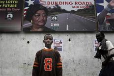 A Liberian child stands in front of an election poster for President Ellen Johnson Sirleaf in the Liberian capital Monrovia, September 8, 2011.   REUTERS/Simon Akam