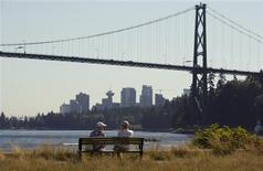 <p>A couple sit on the waterfront facing the Lions Gate Bridge in West Vancouver, British Columbia, September 9, 2011. REUTERS/Andy Clark</p>