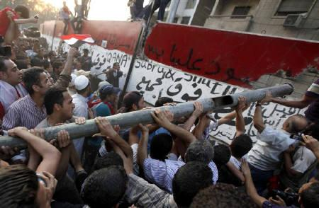 Protesters knock down a concrete wall built in front of the Israeli embassy in Cairo September 9, 2011. EREUTERS/Mohamed Abd El-Ghany