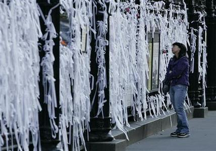 Joanne Sang of New York looks at memorial ribbons tied along the fence of St. Paul's chapel to remember victims of the 9/11 attacks the day before the 10th anniversary of the 9/11 attacks on the World Trade Center, in New York September 10, 2011. REUTERS/Hugh Gentry