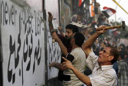 Protesters tear down a concrete wall built in front of the Israeli embassy in Cairo September 9, 2011. REUTERS/Mohamed Abd El-Ghany