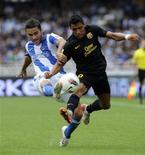 Alexis Sanchez (à dir.), do Barcelona, e Daniel Estrada, do Real Sociedad, lutam pela bola durante partida pela primeira divisão do campeonato espanhol, em San Sebastián. 10/09/2011 REUTERS/Vincent West