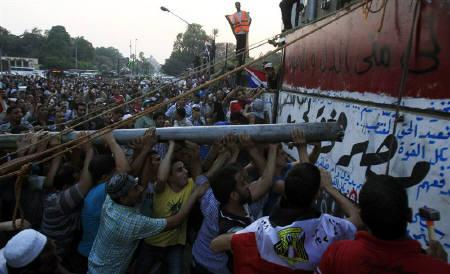 Protesters tear down a concrete wall built in front of the Israeli embassy in Cairo September 9, 2011. REUTERS/Amr Abdallah Dalsh