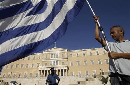 A taxi driver holds a huge Greek flag during a protest outside the parliament in Athens' Syntagma (Constitution) square, July 26, 2011. REUTERS/John Kolesidis/Files