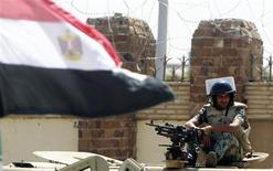 An Egyptian army soldier sits on his vehicle beside an Egyptian flag outside the police academy where the trial of Egypt's former President Hosni Mubarak will take place in Cairo September 11, 2011.  REUTERS/Amr Abdallah Dalsh