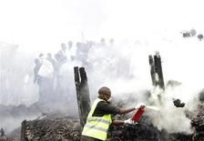 Люди наблюдают за тем, как спасатели работают на месте пожара в Найроби 12 сентября 2011 года. По меньшей мере 61 тело удалось обнаружить на месте пожара, возникшего из-за утечки бензина в густонаселенных трущобах столицы Кении Найроби, сообщила полиция в понедельник. REUTERS/Noor Khamis