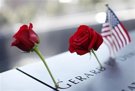 A pair of roses and a U.S. flag are left on one of the panels containing the names of the victims of the attacks on the first day that the 9/11 Memorial was opened to the public at the World Trade Center site in New York, September 12, 2011. REUTERS/Mike Segar