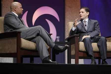 Federal Communication Commission Chairman Julius Genachowski (R) speaks with former FCC chairman Michael Powell at the Cable Show in Chicago, June 15, 2011. REUTERS/John Gress