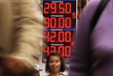 Люди проходят мимо обменного пункта в Санкт-Петербурге, 9 августа 2011 года. Рубль подрастает в начале торгов вторника к бивалютной корзине и дорожает к доллару США благодаря улучшению ситуации на внешних рынках, росту цен на нефть, продажам экспортной валютной выручки. REUTERS/Alexander Demianchuk
