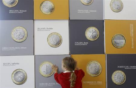 A young girl plays with cubes printed with pictures of Euro coins as part of a 3D puzzle at the German Finance Ministry in Berlin August 20, 2011. REUTERS/Tobias Schwarz