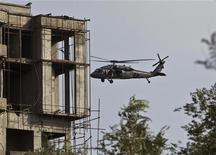 """Вертолет НАТО пролетает возле здания, захваченного боевиками """"Талибана"""" в ходе атаки на посольство США в Кабуле, 13 сентября 2011 года. По меньшей мере четыре взрыва прогремели в столице Афганистана Кабуле близ района, где сосредоточены посольства других государств, после одного из взрывов была слышна стрельба, сообщила полиция. REUTERS/Ahmad Masood"""