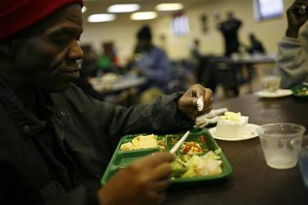 A man eats lunch at the Capuchin Soup Kitchen, where hundreds of people receive food and supplies everyday, in Detroit, Michigan, December 9, 2008. REUTERS/Carlos Barria