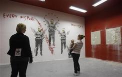 "Visitantes olham obra ""Every Picture Tells a Lie"", do artista de rua britânico Banksy, na galeria Kunstraum Bethanien. 13/09/2011 REUTERS/Tobias Schwarz"