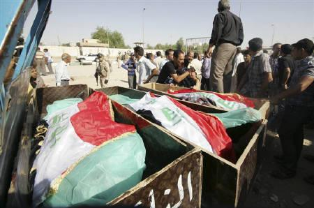 Residents place Iraqi national flags on the coffins of victims killed by gunmen in Kerbala, 80 km (50 miles) southwest of Baghdad September 13, 2011. REUTERS/Mushtaq Muhammed