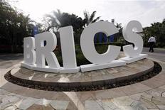"""Мужчина проходит мимо инсталяции """"БРИКС"""", установленной к саммиту в городе Санья (Китай), 14 апреля 2011 года. Страны БРИК могут подумать о наращивании количества облигаций, номинированных в евро, в своих портфелях, чтобы помочь Европе преодолеть суверенный долговой кризис, написала во вторник бразильская газета Valor Economico со ссылкой на анонимного чиновника. REUTERS/Jason Lee"""