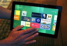 Репортер Рейтер смотрит планшетник с ОС Windows 8 на конференции в Анахайме, США, 13 сентября 2011 года. Microsoft Corp раздала 5.000 планшетников Samsung, работающих на базе тестовой версии Windows 8, на ежегодной конференции разработчиков во вторник, надеясь таким образом подогреть интерес к своей новой операционной системе.  REUTERS/Alex Gallardo