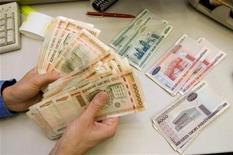 Кассир пересчитывает деньги в банке в Минске, 29 января 2010 года. Нацбанк Белоруссии заявил, что не проводил интервенций на первых свободных торгах валютой в среду, на которых рубль резко упал к доллару, а спрос в несколько раз превысил предложение. Нацбанк надеется, что дополнительная сессия поможет за полтора месяца унифицировать курс рубля и избавит от необходимости просить МВФ о помощи.  REUTERS/Vasily Fedosenko