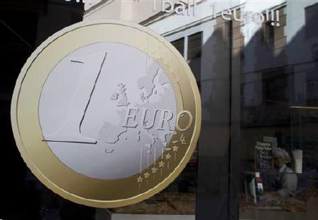 A waitress waits for customers in a pizza shop with a sign of a euro coin in its window in central Madrid, September 13, 2011. REUTERS/Paul Hanna/Files