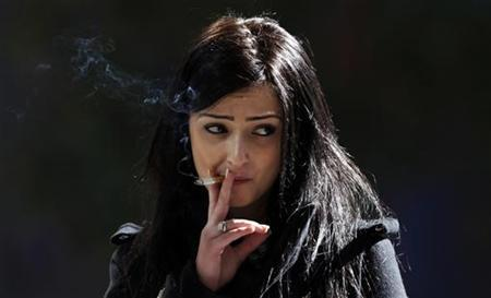 A woman smokes a cigarette outside an office building in central Sydney June 27, 2011. REUTERS/Daniel Munoz
