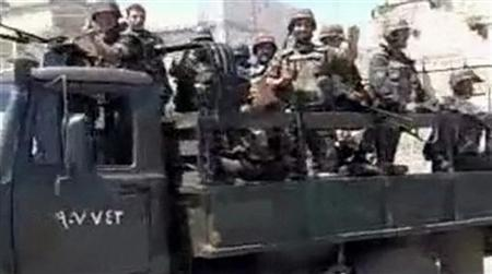 Syrian soldiers wave from military vehicles driving into the Jabal Al-Zawya area of Idlib on August 1, 2011 in this still image taken from video posted on a social media website. EDITOR'S NOTE: REUTERS CANNOT INDEPENDENTLY VERIFY CONTENT VIDEO FROM WHICH THIS STILL IMAGE WAS TAKEN REUTERS/Social Media Website via Reuters TV